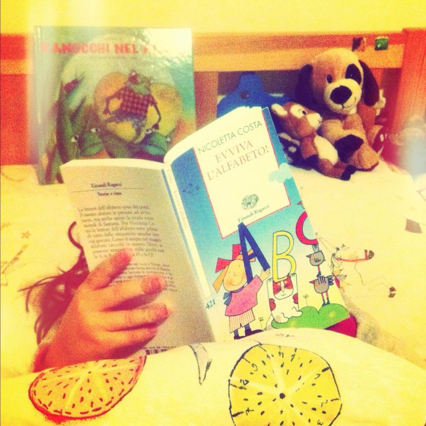 bambina che legge libro sull'alfabeto