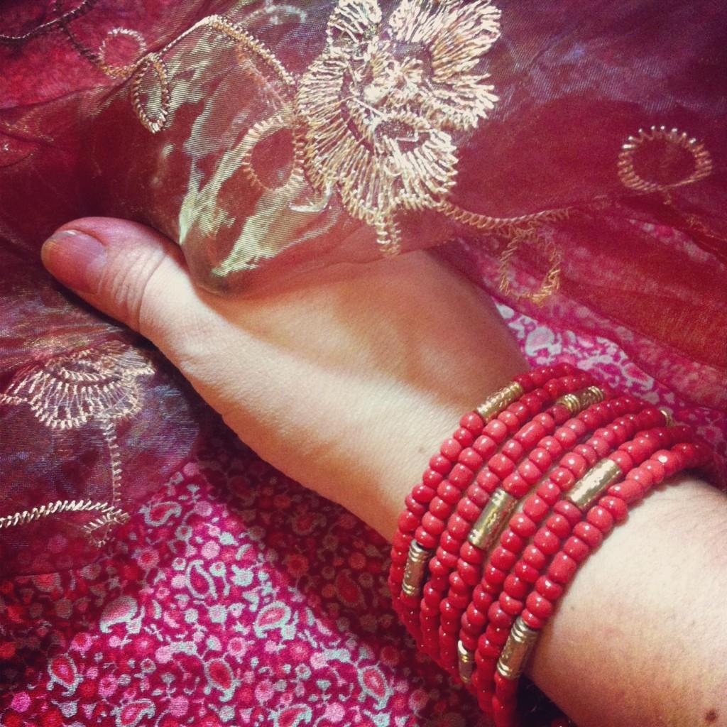 mano con braccialetto rosso pompeiano e altri tessuti rosso/dorato